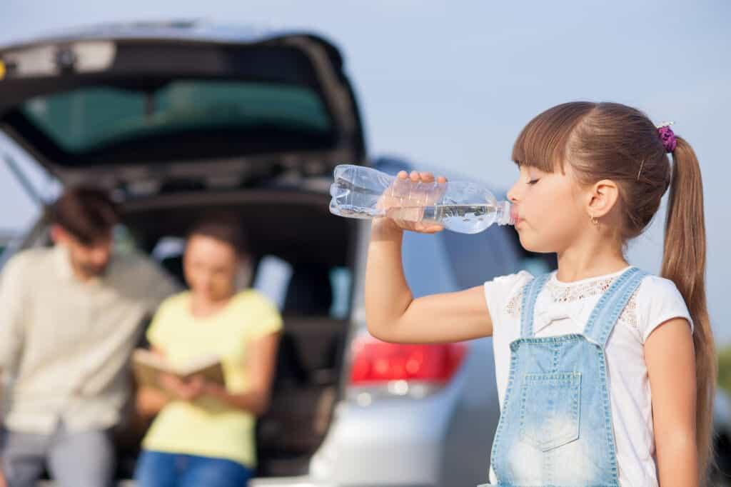 familie på bilferie pige drikker vand mens de holder pause