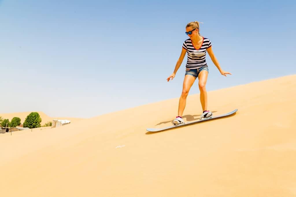 kvinde på sandboard på vej ned af en bakke af sand i økenen i dubai